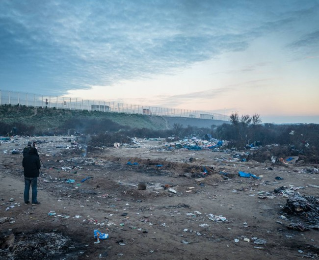 © Rob Pinney 'At dawn, camera crews film an area of the camp evicted by French authorities.'