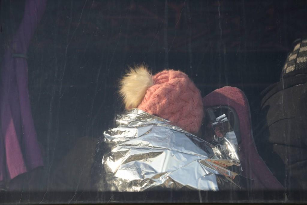 © pink bobble hat, UN refugee transportation bus, Lesbos, Greece