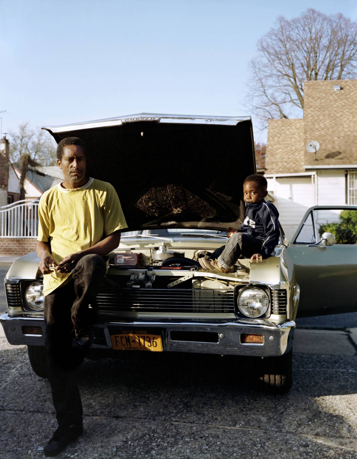 Photo by Elias Williams from his on-going portrait of his neighborhood in Queens, NYC. Greg with his son Jaivyn, spending the afternoon working on their Chevy Nova. Greg, who lived in St. Albans his whole life, witnessed many of his neighbors lose their homes throughout the community's housing crisis. St. Albans, Queens.
